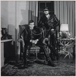Robert Mapplethorpe - Brian Ridley and Lyle Heeter, 1979. Photograph on paper  Humour is not something that we tend to associate with Mapplethorpe's work, but this double portrait certainly has it. Unusually, Mapplethorpe has chosen to photograph these two men not in a neutral setting but in a cluttered environment of questionable taste. The implication is that this is where the men live. They are dressed in full black leather gear and the submissive seated partner is chained up and shackled to the bearded standing figure. The sado-masochistic ritual that is being enacted contrasts totally with the homey living room. The only pointer to darker currents is the table to the right made of deer antlers.