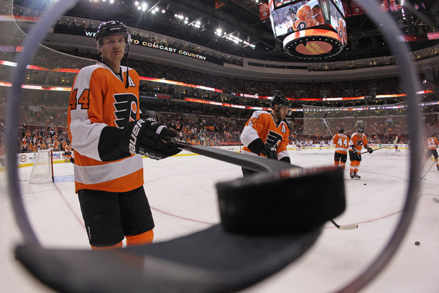 Kurtis Foster of the Flyers passes a puck through a hole to a fan during warmups prior to the game against the Rangers on Tuesday. (Bruce Bennett/Getty Images) POWER RANKINGS: Where do the Flyers rank?