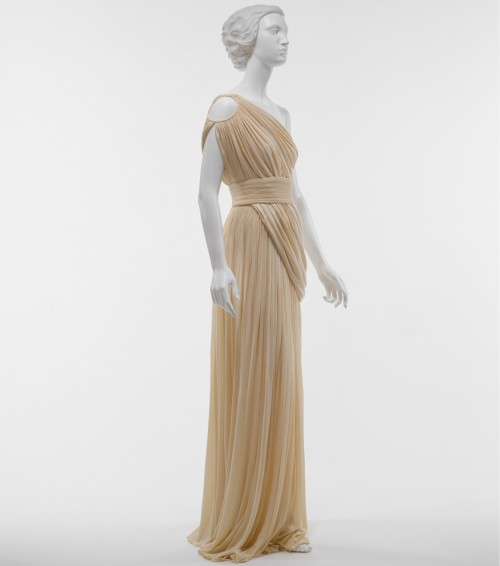 fashioninhistory:  Evening Dress Madame Grès 1967 The collections of Madame Grès were prized for the pleated silk jersey gowns that ended each of her shows. With their himation-like draped swags, these designs are a relaxed version of the fine dense pleating that generally covers her fitted, highly structured bodices. The technical virtuosity incorporated in the draping is revealed only on close study of this example. The swags are both continuous and unbroken panels of fabric that incorporate the right fronts and backs of the gown. In her neoclassicism, Grès conformed to the antique notion of uninterrupted lengths of cloth, stitched but not cut into shape. From her earliest work, Grès introduced windows onto the body with cutouts that bared the back and midriff. She created a fissured shoulder, consistent with her own practice and resonant of the split shoulderlines of antique chitons.- The Metropolitan Museum of Art
