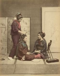 Hairstyling Woman styling the hair of a woman sitting on a tatami, while a third woman is watching. Photo of a series of 42 hand coloured albumine prints at Spaarnestad Photo by Felice Beato, Kusakabe Kimbei or Raimund baron von Stillfried. Japan, around 1880.