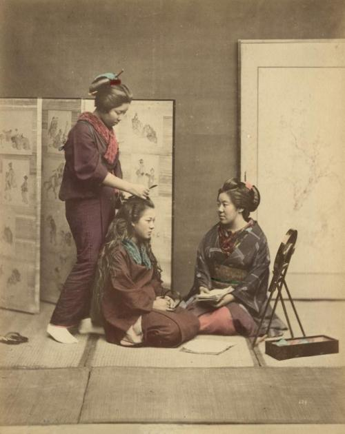 lora-does-things:  Hairstyling Woman styling the hair of a woman sitting on a tatami, while a third woman is watching. Photo of a series of 42 hand coloured albumine prints at Spaarnestad Photo by Felice Beato, Kusakabe Kimbei or Raimund baron von Stillfried. Japan, around 1880.
