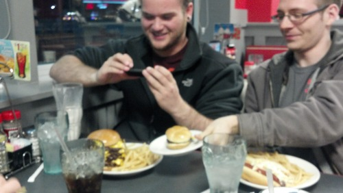 "morethanadreamr sends us, ""My friend taking a picture of his 7x7 burger while another friend compares it to his slider."""