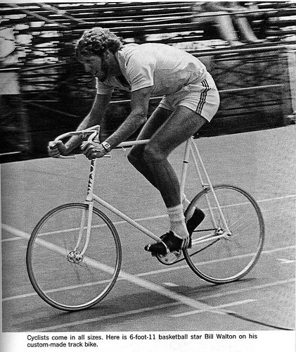 "onabicycle:   NBA legend Bill Walton looking pretty sweet on his track bike in the late 1970's  This photo reminds me of my old bike shop for two reasons. 1. A smarmy shop employee, who we will call ""asshole"", tried to sell NBA MN Timberwolves' Luc Longley (3"" taller than Bill Walton) a 62cm (center to top) road bike that we had ""in stock"". I interceded and set up an appointment with Minneapolis, MN custom bike builder Walter Croll. 2. In appreciation for the business we sent Mr. Croll our employees, including myself, wound up getting free, or at cost, custom track frames which we all deployed at the NSC Velodrome. One of the shop employees crashed Mr. Croll in a particularly vicious Unknown Distance sprint finish that resulted in multiple broken bones and thousands of slivers. How's that for gratitude? (I miraculously bounced off both and finished second.) An aside, I love Bill's slammed stem! The shorts/socks not so much. ""Asshole"" didn't get one of those track frames."