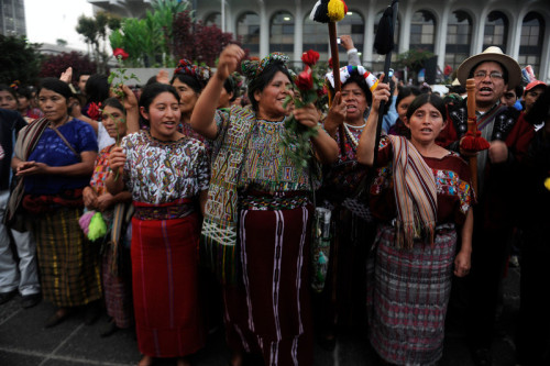 fotojournalismus:  Maya Ixil women, including Guatemala's civil war survivor Maria Raymundo (C), celebrate after listening the sentence given to former Guatemalan de facto President, retired General Jose Efrain Rios Montt, 86, for crimes committed during his regime, in Guatemala City on May 10, 2013. Rios Montt was found guilty of genocide and war crimes on Friday in a landmark ruling stemming from massacres of indigenous people in his country's long civil war. Rios Montt thus became the first Latin American convicted of trying to exterminate an entire group of people in a brief but particularly gruesome stretch of a war that started in 1960, lasted 36 years and left around 200,000 people dead or missing. [Credit : Johan Ordonez/AFP/Getty Images]