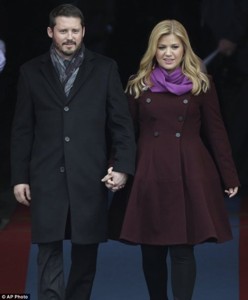 Celebrity Scarf Watch: Kelly Clarkson wearing a vibrant purple scarf and her fiance Brandon Blackstock wearing a grey stars and stripes scarf at President Obama's inauguration.