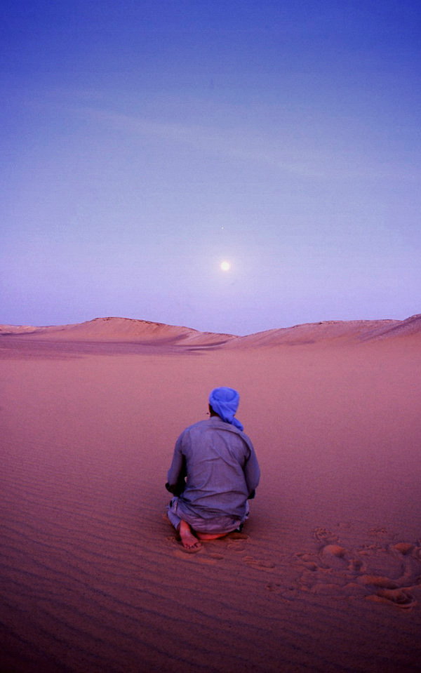 Our Bedouin guide in the White Desert of Egypt, praying at sunset. Venus and the moon line up almost perfectly.
