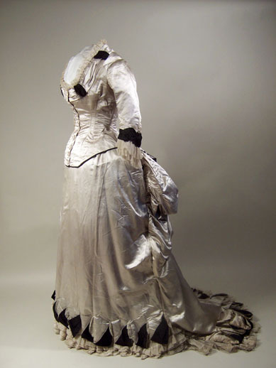 Half-mourning dress by W G Jay & Co, 1883-84 London, Manchester Art Gallery  Half-mourning dress (?) Pale grey satin trimmed with black figured and black corded silk and white net. Two piece.Bodice lined with cream twilled silk. Low square-cut neck. Fastening at centre front with embroidered buttons. Neck trimmed with band and double frill of net. Sleeves shaped to wrist, trimmed with frill of net. Separate skirt lined with stiffened cotton, fastening left back. Hem cut in triangles. Train at back. Lace muslin frill. Tapes and ties at back to form bustle.