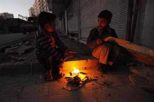 #Syria - Picture: Two boys sit near a fire in the Bustan al-Qaser area in Aleppo; December 26, 2012.
