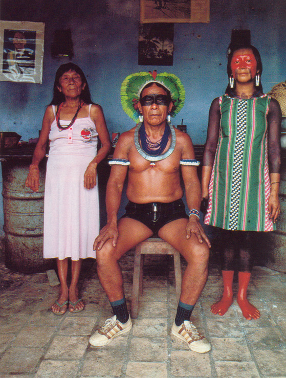 kicker-of-elves:  Kayapo headman flanked by wife and daughter wears a headdress of parrot feathers that denotes family origins, Brazil   National Geographic 1984  Miguel Rio Branco