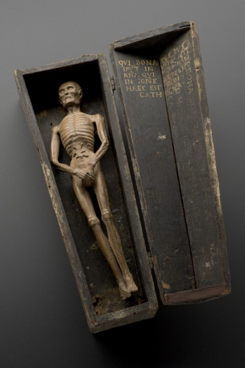 muscavomitoria:  Figure of a man in a coffin, Italy, 1501-1600 Carved from wood, this figure shows a male corpse inside a coffin. The body is in advanced decay and worms are spilling from the stomach. The coffin is a memento mori. This is an object that reminds the viewer of the shortness of human life and the inevitability of death.