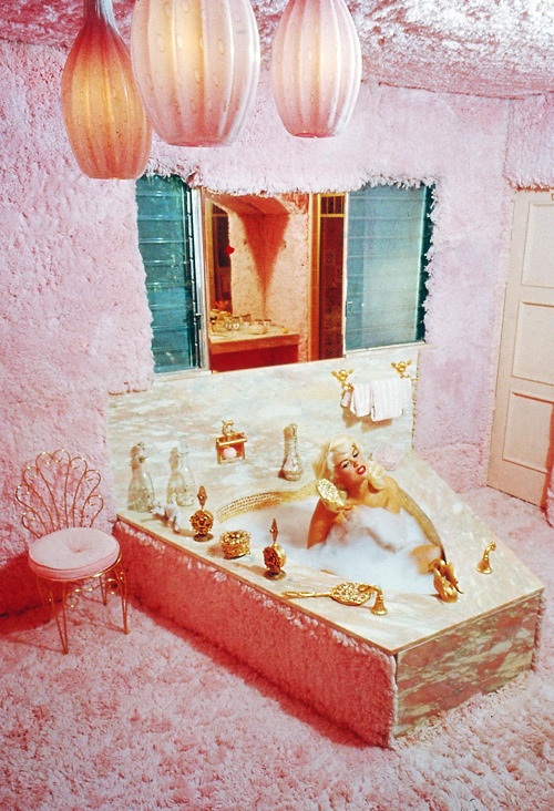 "vintagegal:  Jayne Mansfield combs her hair while bathing in the pink carpeted bathroom of her home, known as ""The Pink Palace,"" in Los Angeles, 1960."
