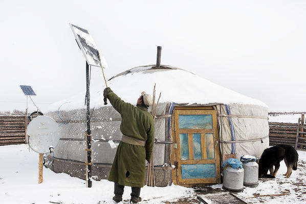 ninewhitebanners:  A Mongolian nomad brushes snow off solar panels outside his ger after a blizzard. Gers are heated by stoves burning coal or animal dung, but solar power can charge cell phones and run tvs and lights. Photo by Taylor Weidman.