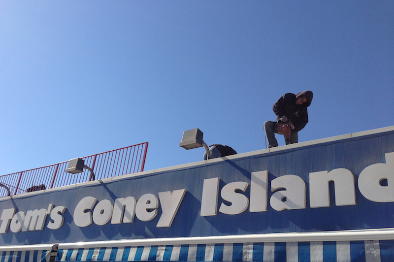 A construction worker on the roof of the restaurant Tom's Coney Island. Tom's faces the boardwalk but somehow managed to escape severe damage from Hurricane Sandy. They held a benefit for their less fortunate neighbors late last year to aid in the community's recovery. The boardwalk's businesses are set to be fully operational by summer. (The Brooklyn Ink/Richard Feloni)