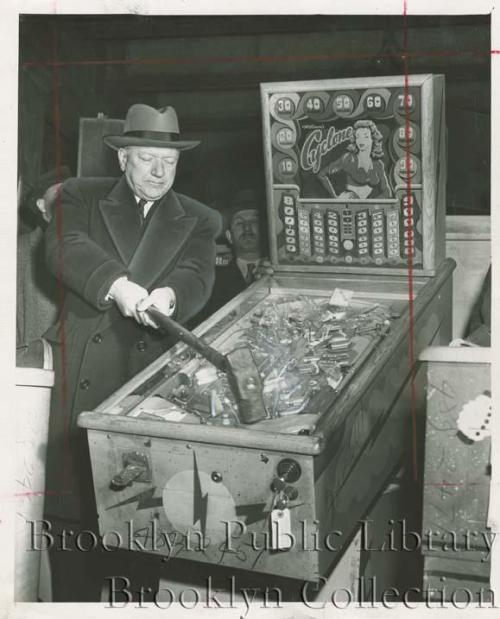 "Police Commissioner William O'Brien destroys a pinball machine with a sledge hammer in Brooklyn, circa 1949. Mayor Fiorello La Guardia ordered police to smash pinball machines, alleging that ""pinball is a racket dominated by interests heavily tainted with criminality."" The Atlantic's Conor Freidersdorf wrote a great piece about the hysteria and ""moral panic"" surrounding New York City's anti-pinball craze:   The fact that…zealous paternalism robbed fellow citizens of an amusement, despite its by-now-self-evident harmlessness, isn't a reason to condemn them. It is, rather, a reason to tread carefully when we codify our own judgments into binding municipal law. Pinball bans seem unbelievably absurd today. What regulations will seem equally needless to future generations?    Source"