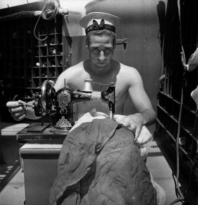 elevenacres:  A Royal Navy sailor on board HMS Alcantara uses a portable sewing machine to repair a signal flag during a voyage to Sierra Leone, March 1942, Cecil Beaton, English (1904–1980). © The Imperial War Museums