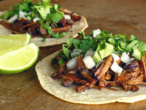 prettygirlfood:  Tacos de Barbacoa INGREDIENTS 1/3 cup  cider vinegar 3 tablespoons lime juice 3-4 canned chipotle chiles 4 cloves garlic, roughly chopped 3 1/2 teaspoons ground cumin 2 teaspoons dried Mexican oregano 1/2 teaspoon ground cloves 1 1/2 teaspoons freshly ground black pepper 1 1/2 teaspoons table salt or 3 teaspoons Kosher 2 tablespoons vegetable oil 4 pounds boneless chuck roast, excess fat removed 3/4 cup chicken broth, plus more as needed 3 bay leaves 20 warm corn tortillas Diced white onion, chopped cilantro and lime wedges for garnish METHOD Preheat the oven to 275°. Combine the cider vinegar, lime juice, chipotle chiles, garlic cloves, cumin, oregano, clove, black pepper and salt in the bowl of a food processor or blender and puree until completely smooth — about a minute or so.  Transfer the spice paste to a bowl and set aside. Dry the roast all over with paper towels, cut away any excess fat and slice the meat into 4 evenly sized pieces.  Heat the 2 tablespoons of oil in a very large pot set over high heat until it begins to shimmer.  Working in batches if necessary, sear the beef on all sides until deeply browned, about 10 minutes. Add the chile puree to the pot and stir until the beef is well-coated.  Add the chicken stock and bay leaves and bring the liquid to a boil.  Reduce the heat to a simmer, cover the lid with tin foil and add the lid to create a very tight seal.  Place the pot in the oven and braise the meat for 5-6 hours, removing the lid during the last hour or so to allow the simmering liquid to reduce slightly. Allow the beef to cool slightly, spoon off any easily removable fat from the braising liquid and then use two forks to pull/shred the beef into bite size pieces. Taste and adjust as necessary for seasonings.  Serve spooned onto warm corn tortillas topped with diced white onion, chopped cilantro and lime wedges for garnish. Makes about 20 tacos