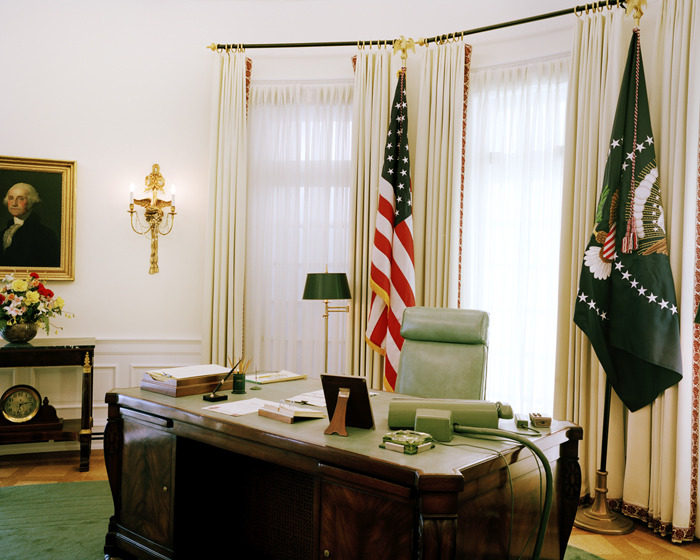 "The Oval Office 7/8th Scale ""Johnson kept abreast of the news with a teletype machine and three screen simultaneously"" Lyndon Baynes Johnson Museum & Library, 2012  by Elizabeth Shear  The Oval Office 7/8th Scale is not a photograph of the Oval Office, but a photograph of a model. Removed from its original referent (the Oval Office in the White House in Washington, DC during Johnson's Presidency), the photograph provides interplay between depiction, reality and assumed knowledge. Photographing is just another method of copying (here an already copied model) and the result is not an image of historic significance, but rather a text that provides a chance to look at representation, its history and its role in our understanding of the past. Postmodernism appropriates the past in fragments and Elizabeth Shear's work borrows directly from history's representation. But as postmodernist works become divorced from their actual historical moments because of conflicting information and signs within them, this photograph divorces us from the moment in history when Lyndon Banes Johnson was in office. The museum (through its model) provides a chance to experience what is no longer even a possibility: a glimpse into the past and a surrogate that simulates the experience we can't have. The Oval Office 7/8th Scale becomes a critical examination of contemporary society's willingness to accept the simulacra in place of the authentic as a real and useful model for learning about the thing it represents. Elizabeth Shear holds a BFA from the Art Institute of Boston and has exhibited throughout the Boston area. Her book, The Shape of Things, is forthcoming. for more, please visit www.elizabethshear.com"