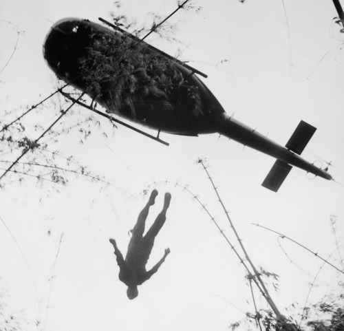 zaksphc:  The body of an American paratrooper killed in action in the jungle near the Cambodian border is raised up to an evacuation helicopter in War Zone C, Vietnam in 1966. Photographed by Henri Huet.