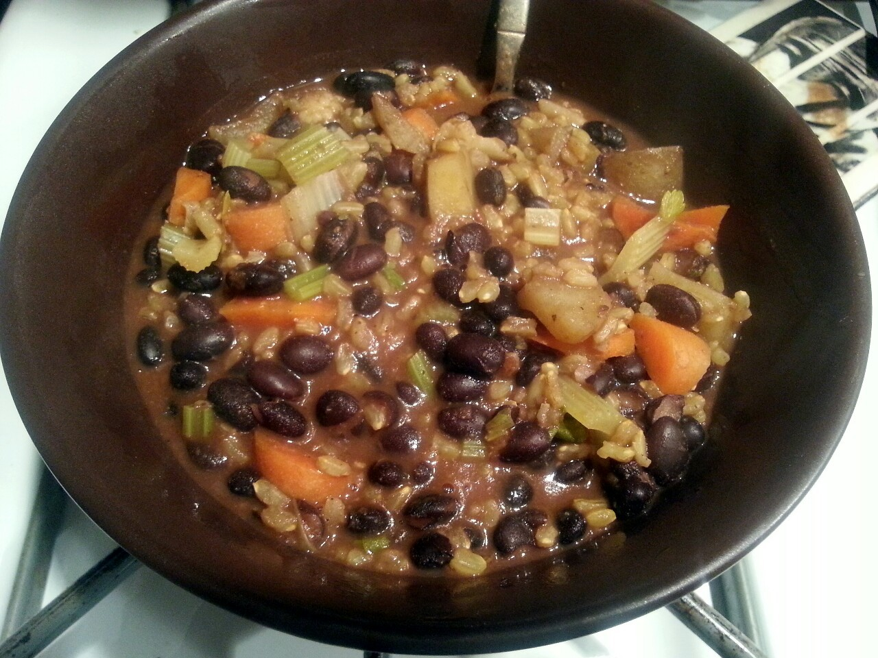 Chunky Black Bean Stew with Carrots, Potato, Celery and Brown Rice.  I soaked about 2 cups of dried beans overnight and then rinsed them and brought them back to a boil over new water. Then I simmered them for about 45 minutes to an hour with 2 tbls garlic, 1 tbls cumin, 1.5 tbls chili powder, and cayenne to taste.  I actually used leftovers from the potato casserole I made the night before to add to the beans, but you can bake about 4 potatoes, 5 carrots, and 5 stalks of celery for about 30 minutes before adding them to the beans. Add the veggies after beans have simmered for 45 minutes, and then let it all simmer with an added cup of veggie broth, salt and pepper to taste, and a dash more garlic, cumin, and cayenne. Cause I like it hott.   Let it simmer uncovered if you want it super thick, or keep covered to hold on to more of the broth.   Serve and eat with a bunch of tortilla chips if you want to get serious.