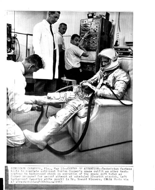 "lightthiscandle:  5/15/63: ""Center of Attention: Technician fastens boots to complete astronaut Gordon Cooper's space outfit as other technicians in background check on operation of the space suit today as Cooper prepared for second attempt at scheduled 22-orbit mission. Left background (wearing white smock) is Dr. Howard Minners."""