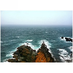 "Misty, mystical, magical wonders at the #Yehliu Cape of the #Geopark.  This is my #view of the #sea from the pavillion located at the tippy top of #GueitouMountain (""Turtle Head"") at the furthest north point out on #Yehliu Cape…except, apparently, we could have gone a little further out to THAT point if we dared. What you can't see in this photo are two tiny fishermen down at the tips of those rocks down there.  The waves are strong, unpredictable, deadly, and dangerous, yet we saw a handful of fishermen along the backside of the park as we approached this point. (To repeat myself from the previous post):  We hiked up the steep side of the mountain (which we later found out was actually ""closed off"") and kept following the steps up and up behind each turn.  Our curiosity took us to the top and we were pleasantly surprised with a gorgeous full view of Yehliu Cape and a lookout of the vast sea and #horizon.  The winds were strong and the sky was grey.  It gave a very two dimensional look to some of our photos, yet a very mysterious and mystical feel while we enjoyed our view from above. #water #ocean #waves #travel #taipei #taiwan #asia #台北 #台灣 #野柳 #萬里 #野柳地質公園  (at Yehliu Geopark 野柳地質公園)"