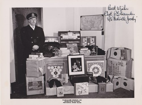Captain P.E. Saunders poses on the S.S. Melville Jacoby with the books, records, games and photos donated to the ship's crew by Elza Meyberg, Melville Jacoby's mother.