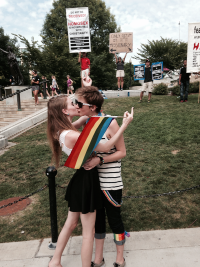 """penicillium-pusher:  dolofang:  compassfox:  drop-bass-not-babies:  Nothing says """"I support gay equality"""" like a straight couple kissing in public.  … I'm a girl We're both girls  nothing says """"I support equality"""" like assuming someone is a boy because they have short hair   ok but the """"Only Gets it Missionary"""" sign"""