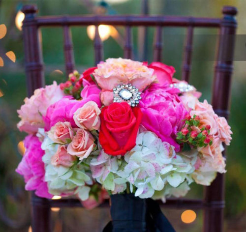 Beautiful and fragrant roses, peonies, spray roses, combined with hypericum berries and antiqued hydrangea blossoms, accented with heirloom broaches - a lovely bridal bouquet. Image by Castaldo Studio