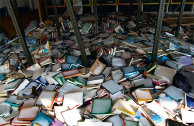 Snow on books that has fallen through the smashed floor to ceiling windows of a now abandoned school library.