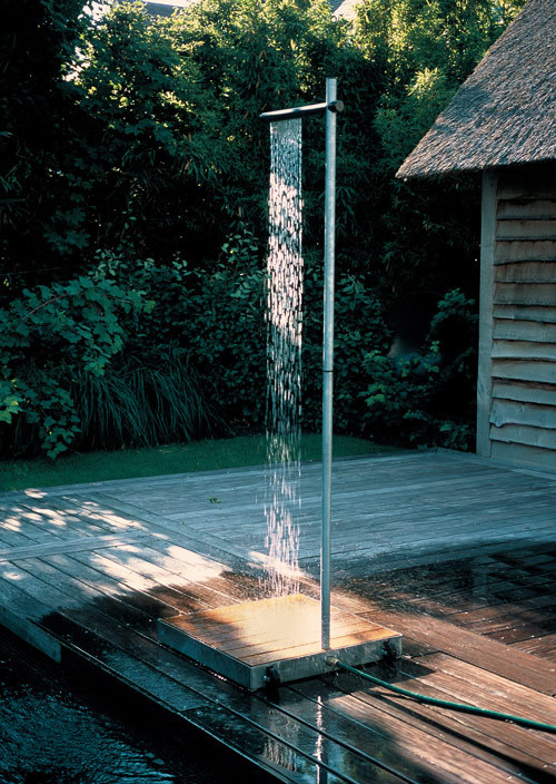 Outdoor Shower by TradeWinds  Cascade is an outdoor shower for terraces and gardens made out of hot galvanised steel. The acacia wood base planks are comfortable and friendly to bare feet.  A discreet tap on the vertical tube regulates the shower's pressure and the overhead horizontal tube provides a sheer waterfall curtain of water. It is easy to connect to a garden hose with a quick connector.