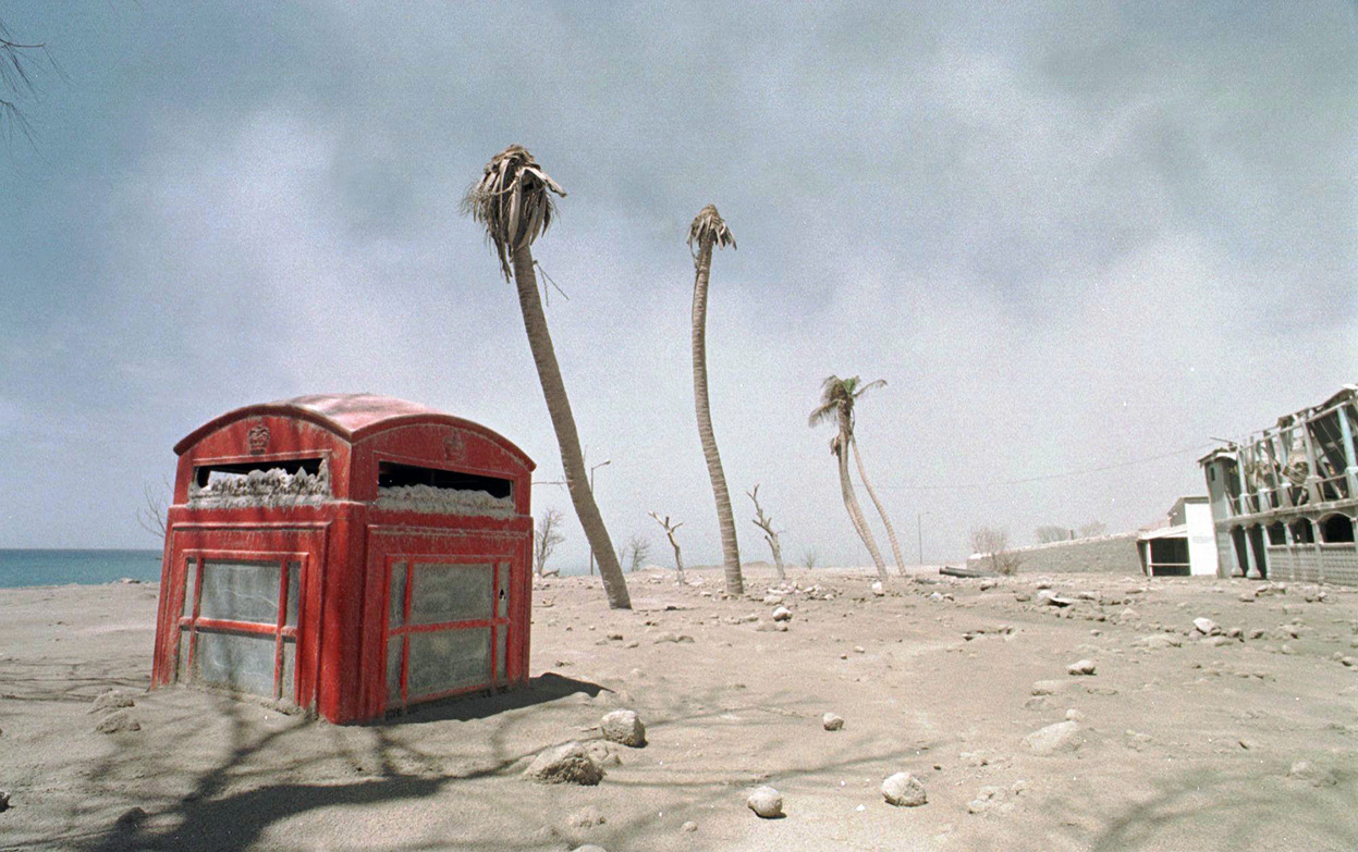 'A traditional British phone booth lies half buried in volcanic ash in the deserted town of Plymouth, on March 2, 1998.' (AP Photo/Gregory Bull)  Soufriere Hills Volcano