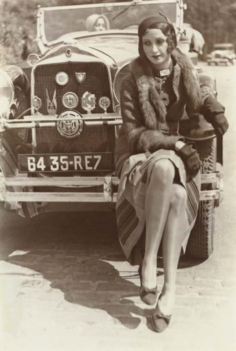 Flapper on a car bumper.  1920s.