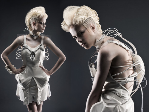 "Anouk Wipprecht - CODAME Featured Artist What does fashion lack? ""Microcontrollers"" according to Dutch based fashiontech designer and innovator Anouk Wipprecht. As she is working in the emerging field of ""fashionable technology""; a rare combination of fashion design combined with engineering, science and interaction/user experience design, she created an impressive body of tech-enhanced designs bringing together fashion and technology in an unusual way. She creates technological couture; with systems around the body that tend towards artificial intelligence; projected as 'host' systems on the human body, her designs move, breath, and react to the environment around them. Part futuristic, part anime-meets-high fashion, her aesthetics are set apart from more utilitarian wearables (which are all about function) and can be considered artistic creations in themselves. Many of her designs have been exhibited in exhibitions as well as fashion events. In Anouk's designs the technology creates the aesthetics as opposed to simply enhancing a function which is hidden. Keen on showing the nuts and bolts of the garments (often the valves and mechanisms are displayed on the outside) we witness the designs creating their own unique forms of interaction, movement and meaning. Wipprecht is an artist, designer, curator and lecturer (Netherlands, China, Austria) in electronic couture, worked for names as the Black Eyed Peas, SuperBowl 2011, Eurovision 2012, with work featured in international magazines. She is the brainchild and curator of the TECHNOSENSUAL 'Where Fashion meets Technology' exhibition, with attached Artist in Residency program to stimulate the grow of fashiontech projects coupling fashion designers and engineers together, that took place in Vienna/Austria over the summer of 2012 and attracted 32.000 visitors in a two and a half month time span. She is currently based in Vienna/Austria, and travels between Amsterdam (NL), Los Angeles (USA), San Francisco (USA) and Montreal (CA). Photo (top) by Jean-Sébastien Senécal. DareDroid 2.0 cocktailmaking robot dress by fashiontech designer Anouk Wipprecht in collaboration with Jane Tingley and Marius Kintel. Meet Anouk at our CODAME FASHION+MUSIC Event June 26th, 2013 from 7pm-2am at Public Works, San Francisco."