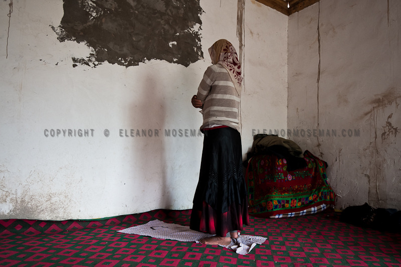 A Uyghur woman prays towards Mecca in her home. Uyghurs, as all Muslims, pray at least 5 times a day. Near Kasghar, 2012