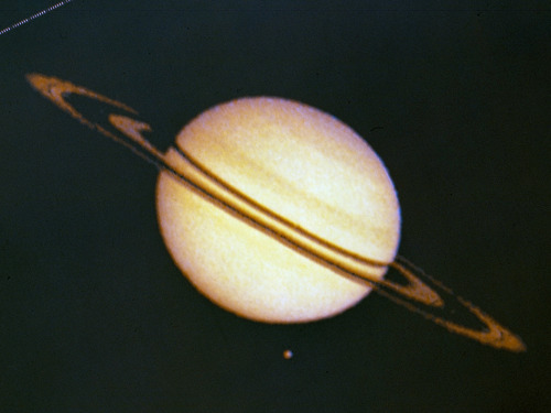 "Pioneer 11 Image of Saturn and Its Moon Titan The Pioneer 11 spacecraft launched from Cape Canaveral forty years ago, on April 5, 1973. Pioneer 11's path through Saturn's outer rings took it within 21,000 km of the planet, where it discovered two new moons (almost smacking into one of them in September 1979) and a new ""F"" ring. The spacecraft also discovered and charted the magnetosphere, magnetic field and mapped the general structure of Saturn's interior. The spacecraft's instruments measured the heat radiation from Saturn's interior and found that its planet-sized moon, Titan, was too cold to support life. This image from Pioneer 11 shows Saturn and its moon Titan. The irregularities in ring silhouette and shadow are due to technical anomalies in the preliminary data later corrected. At the time this image was taken, Pioneer was 2,846,000 km (1,768,422 miles) from Saturn. Image credit: NASA Ames"