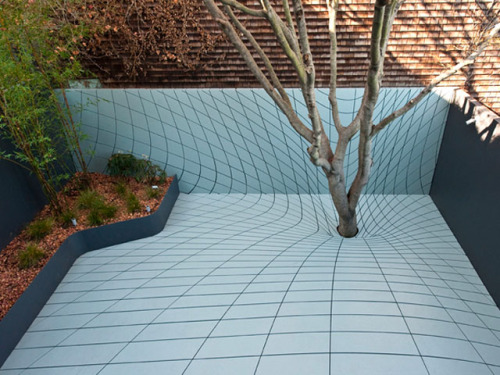 letsbuildahome-fr:  DEFORMSCAPE by Faulders Studio Deformscape is an outdoor extension to a private dwelling in San Francisco. Situated in a tightly packed urban neighborhood, this limited space outdoor sculpture garden inherits a large tree, and uses this sole arboreal presence to establish a gravitational pattern of grooves that are focused towards the tree's centroid. This asserts the valued presence of the carbon-absorbing tree and its green canopy overhead, while allowing for a maximum of usable surface area below free of other vegetation. To generate the resultant pattern, a 3-dimensional bulge is formed around the tree, and its distorted wire-grid projected onto a 2-dimensional surface. Taking into account appearance effects created by perspective views from inside, the resultant planar surface appears sink around the tree.