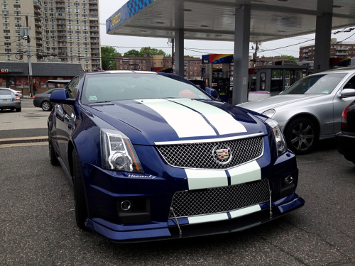 "Heavenly CTS-V Coupe While visiting a friend in Jersey this weekend, I stopped to get some cheap gas and saw this Cadillac CTS-V Coupe. After talking with an employee, I found out that the owner of the car also owns a new Camaro and a Plymouth Prowler (both of which I've seen before)… but this is my favorite out of the three. If you look closely, you'll notice a strange tint to the racing stripes. It's because they're glow-in-the-dark. And those little stickers on the front, rear, and sides that look like they read ""Hennessey"" actually say Heavenly. I asked about it because he has those stickers on the other cars as well, but the guy didn't know why. Wonder what upgrades it has underneath?"