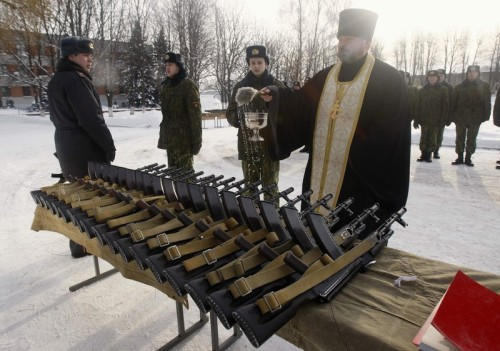 May these weapons send your enemies to their God… An Orthodox priest blesses rifles during a ceremony where new recruits receive their weapons at a military unit of the Belarussian Interior Ministry in Minsk, January 27, 2012.