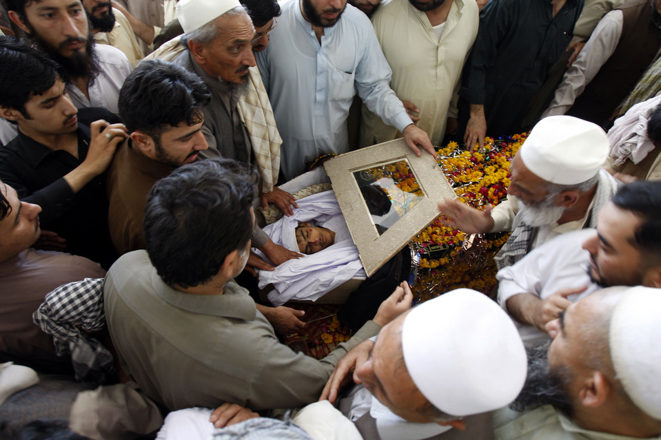Men looked at a victim of a suicide attack during a funeral in Peshawar, Pakistan, Wednesday. A Taliban bomb attack targeting an election rally of the secular Awami National Party killed at least 16 people in Peshawar on Tuesday. Mohammad Sajjad/Associated Press