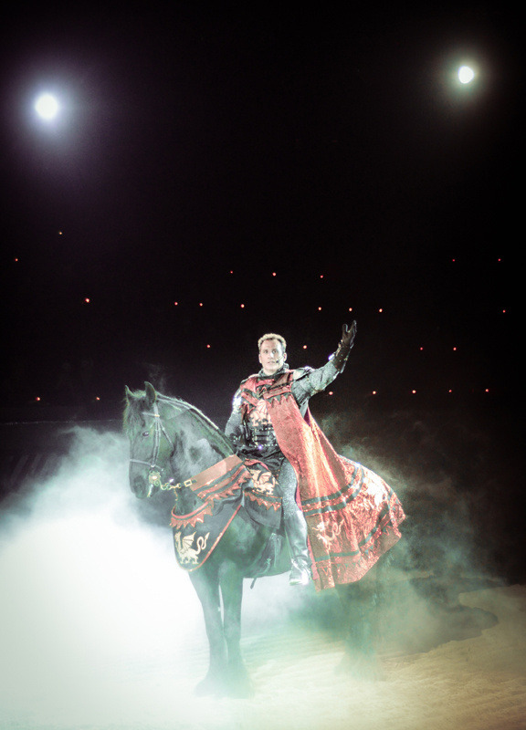 "The Honors and Duties of Knighthood at Medieval Times Blood sport has been an important part of cultures across the globe for centuries. The Romans congregated in the Coliseum to watch gladiators murder each other for spectacle, the Spanish come in droves to watch matadors challenge and flay wild bulls, and Mexican cartels are forcing their kidnap victims to fight to the death. As long as people have been gathering to watch spectacles, those spectacles have included violent displays that tickle the innate human desire to watch things get killed. Although the physical toll of being a Medieval Times jouster is a teeny tiny bit less extreme than the activities mentioned above, it requires far more skill and dedication than an outsider would guess.  Max Shkvorets was a friend of mine in high school. Part of the drama clique, he was the kind of happy-go-lucky kid that bordered on annoying most of the time thanks to his perpetually cheerful attitude. I remember him trying out for our school's improv team (yes, my school had an improv team) and absolutely bombing the audition. He loved acting, but just didn't have the confidence at the time. He was a good guy to be around, but like most friendships at that age, it didn't survive graduation. One day a few years down the line, a mutual acquaintance told me that of all the dramatic hopefuls we studied with, he was one of the very few who managed to get a paycheck for his craft. Not only that, but his day job now required him to wear plate armor and ride a horse—my friend Max had become a knight. Medieval Times is kind of a weird place to work. While most of the people they employ are cooks, servers, or general event staff, the whole operation revolves around the few people—mostly trained actors and stuntmen—with the skill and dedication necessary to perform in the weekly shows. Becoming one of these rare individuals is not an easy task. It requires an intense dedication to something most of us would never even consider trying (or watching, probably).  The first stepping stone to becoming a knight at Medieval Times is temporary employment as a squire. You'll tend to the horses, help load the weapons, and set up and take down various props and effects for the show. It's not glamorous, but it's a foot in the door. The real benefit is the training you recieve from the rest of the crew on stuff like fight choreography and not getting trampled to death by horses mid-show. According to head knight Sean Delaney, not everyone's got the drive for it. ""Part of it's the dedication; part of it's the ability. We've had some people come here with all of the ability but no ambition, and they just fall by the wayside. Then we've had people with nearly no skill who come and get it because they try their guts out. It's those people who are willing to learn as much as they can, ride as hard as they can, and try as hard as they can who make it."" When Max started as a squire a few years back, he was faced with a very typical problem for newcomers to the show. He had some acting ability, but most of the specialty work needed for the show was foreign to him, and training time can be exceptionally rare. ""A lot of it was an uphill battle. When I started as a squire, there were a fair number of them here and most of the training time goes to those who prove themselves. It makes sense to train the guy who's been here for a while rather than the guy who might leave in a month. You sort of have to fight for training time, so I had to go to Sean every day and ask if rather than wash horses for a bit I could do mock tests to become a knight. You just need to keep pushing for it and pushing for it. It's cool how this job puts your advancement in your own hands, but you have to own it. It's definitely made me a stronger person. It's made me understand that you can't wait for people to offer you something—you just need to go out and do it."" Continue"