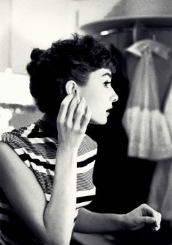 Audrey Hepburn adjusts her earings, photographed by Bob Willoughby, 1953.