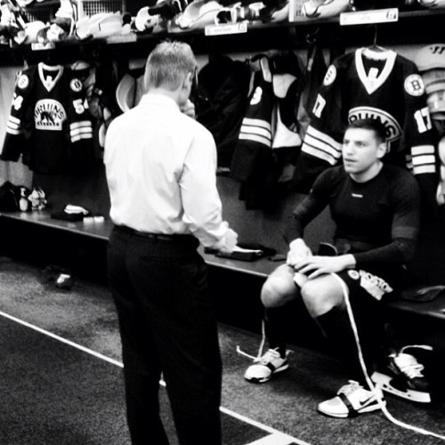 Milan Lucic laces up his skates while chatting with Coach Ward before today's game. #nhlbruins