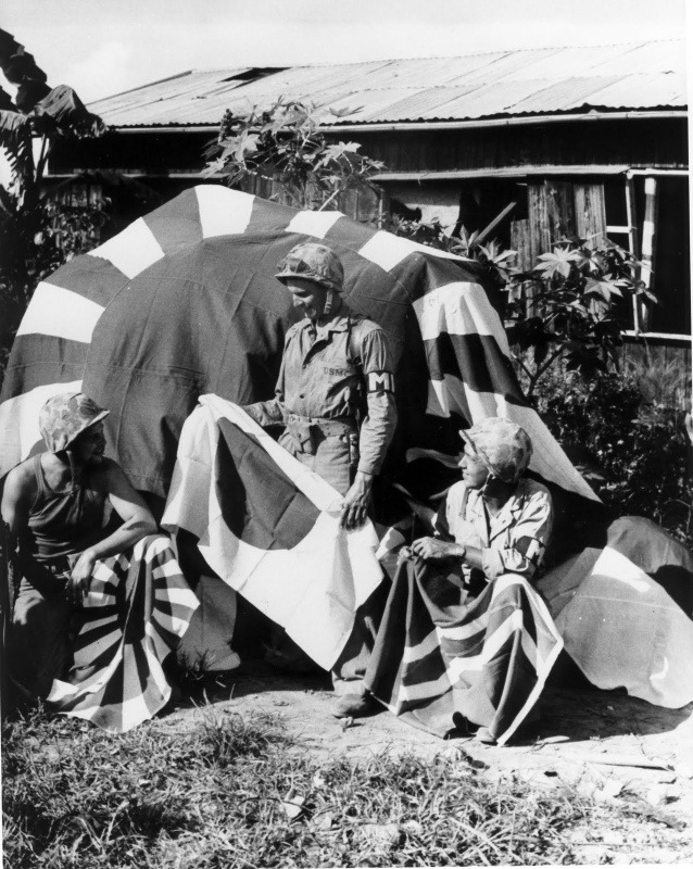 U.S. Marines on Saipan with some captured Japanese flags.