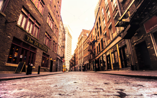 "Stone Street. New York City's first paved street. Financial District.Stone Street is a narrow cobblestone alley that was first developed by Dutch colonists in the 1600s. Its claim to fame is that it is New York City's first paved street and as such it is recognized as a historic landmark.   It's the main part of an area currently known as the Stone Street Historic District. Nestled among skyscrapers in the Financial District, it's something of a time machine back into another era of New York City's history. The street is the site where British merchants traded and sold goods, where American colonialists passionately spoke of independence and where tracts of land were purchased and sold (completely disregarding the earlier inhabitants of the area).   The Dutch West India Company first sold this area to European property owners in the mid 1600s. It was around 1658 that the street was paved. The name Stone Street actually came about in the late 1700s. Prior to being named Stone Street, this alley was called Hoogh Straet and then Brouwer Street and also spent some time as Duke Street. Since the street is so close to the waterfront, it was the site of a tremendous amount of commercial activity for two centuries.  In the mid 1800s, the area was destroyed by the Great Fire. Even though the Great Fire leveled hundreds of buildings in the area, the Stone Street district bounced back due to New York City having the leading maritime port in the country. However, in the mid twentieth century the area saw a decline due to maritime activity moving to the west side of Manhattan. In the mid 1990s, funding was secured to restore the area back to its former glory.     —-Shot with the Sony a99 a few days ago on a bitterly cold winter day here in New York City, I can't think of a better time to experience this historic alley. It comes to life in the summer when it is full of chairs and tables linked to the many dining establishments that now inhabit the buildings along Stone Street. But it's in the winter when the light barely reaches through to the ground and when the breeze from the river cuts through to the bone that it makes an indelible mark on the heart.—-View this photo with a comment thread on my Google Plus page—-Buy ""Stone Street - New York City"" Posters and Prints here, email me, or ask for help."