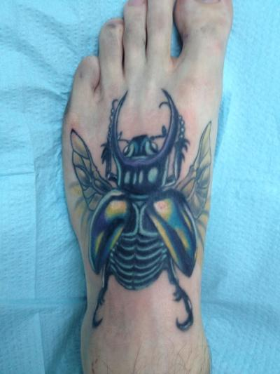 I got this tattoo for my mom who loves scarabs. I had a horrible existing tattoo on my foot and one day I asked my mom what i should get to cover it, and she suggested this. She is my hero so its only fair i got something to represent her. The pain was worth it. Took 4 two hour sessions to finally finish it up. Done by Harvey Deal at Ink Spot tattoo in North Port Florida