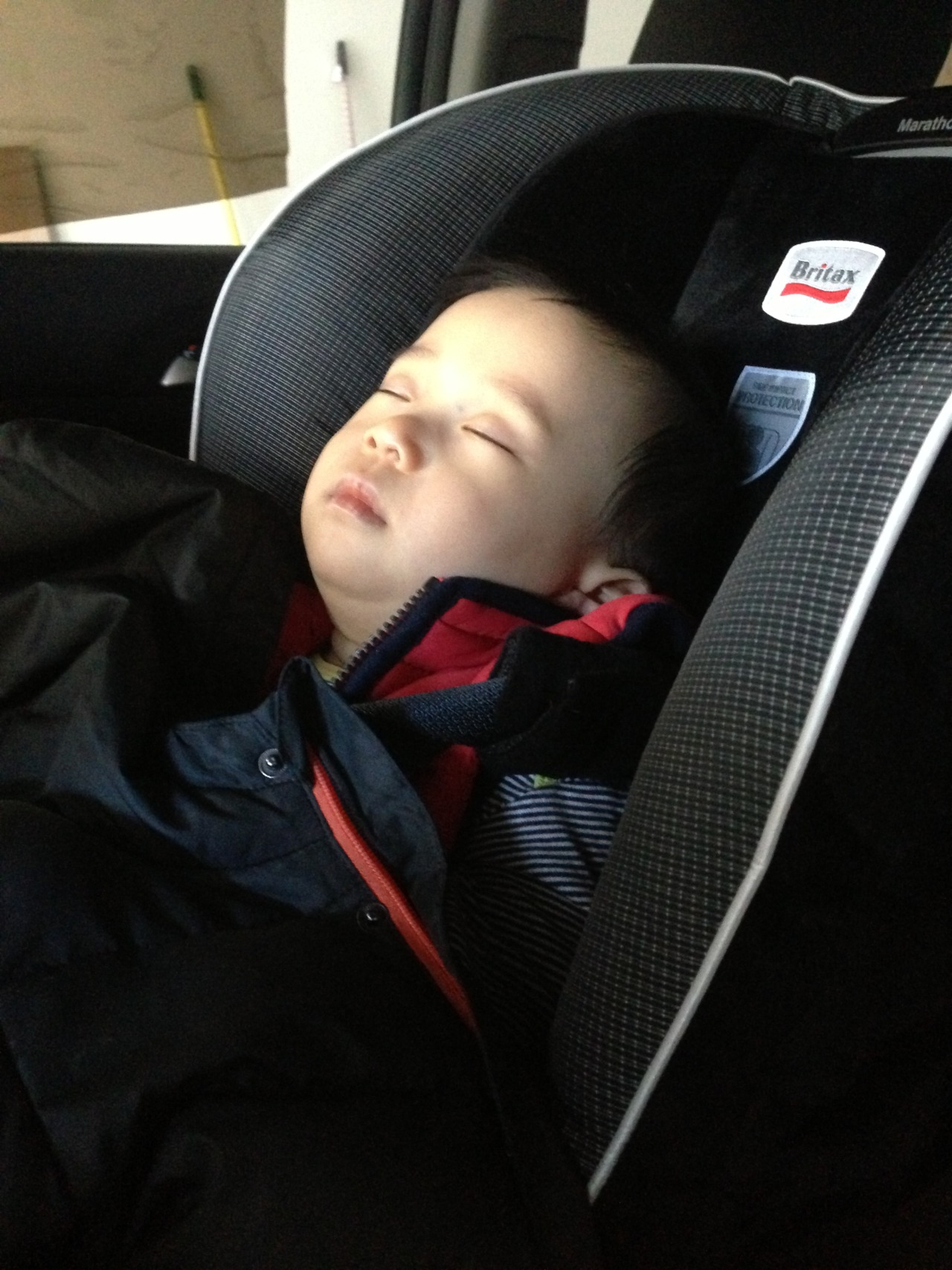 Sleeping in his new car seat!
