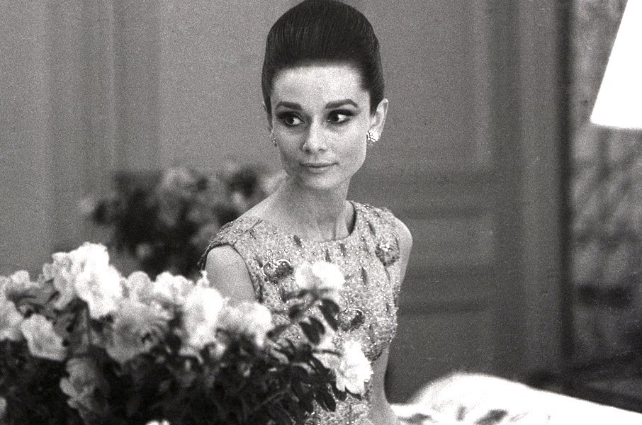"thefashionofaudrey:  The actress Audrey Hepburn photographed by Angela Williams in her suite at Hôtel Ritz, in the same day of the premiere of ""My Fair Lady"" at Théâtre du Châtelet in Paris (France), on December 22, 1964. -Audrey was wearing an evening gown of Givenchy (of his haute couture collection for the Autumn/Winter 1964/65) and Cartier earrings."