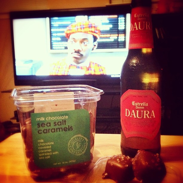 unwinding after a 13 1/2 hour shift: #estrelladamm #daura #beer, milk #chocolate #seasalt #caramel, and #eddiemurphy's #comingtoamerica #myerrrthinghurts