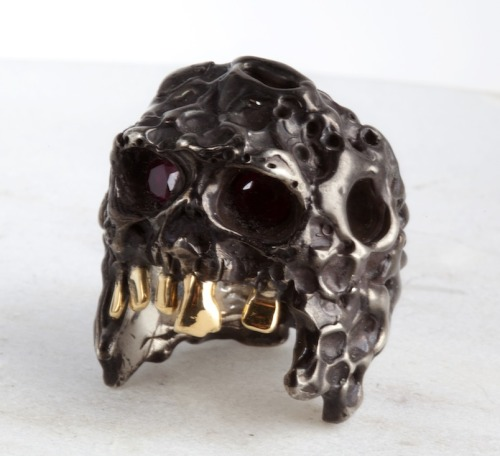 The Skull Ring, silver with Pigeon blood red rubies and 18k gold teath from the tooth fairy. Also, a dark patina that covers the ring and it's crater like surface.