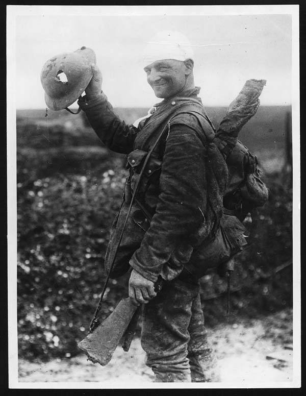 Lucky WWI British soldier shows off his damaged helmet (Western Front, 1917).